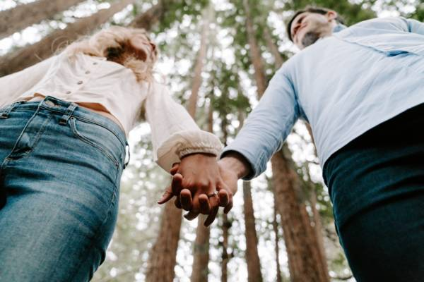 shalow focus photo of man and woman holding each others hands