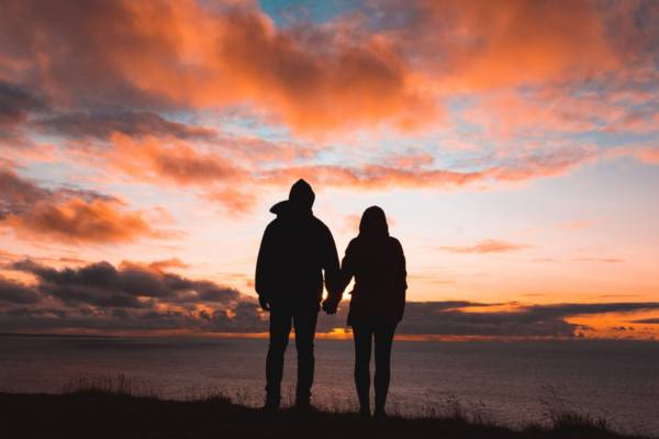 silhouette photo of man and woman on cliff