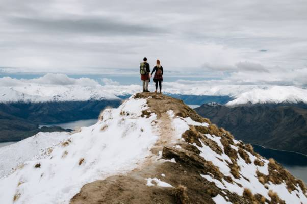 2 men standing on rocky mountain during daytime